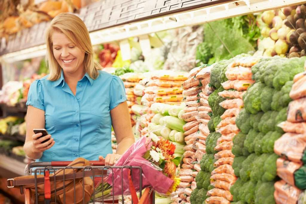 SMILING WOMAN USING MOBILE PHONE IN SUPERMARKET