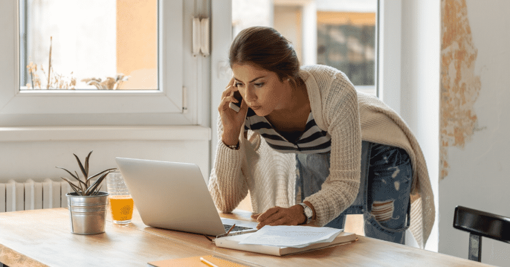woman using a mobile phone while working on a laptop